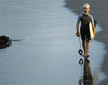 Surfer walking on wet sand