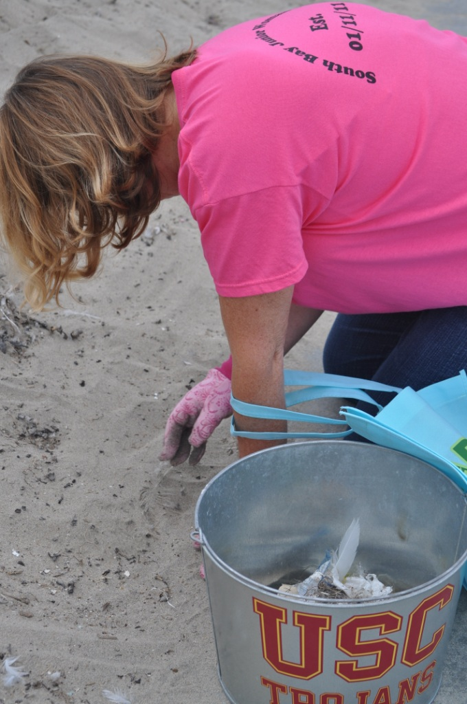 Woman picking up tiny trash at Torrance with reusable gloves and bucket