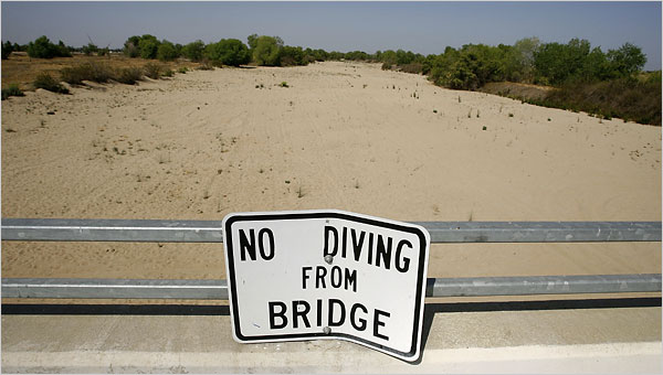 New York Times - dry river-bed with No Diving sign on bridge